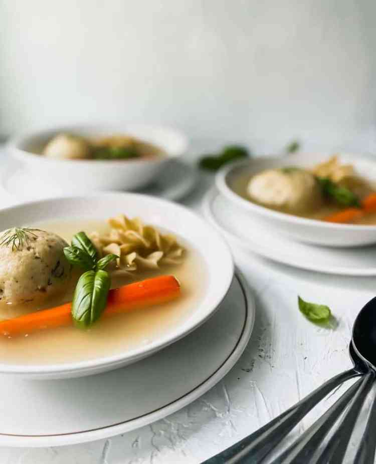 3 bowls of matzo ball soup with metal spoons on the side