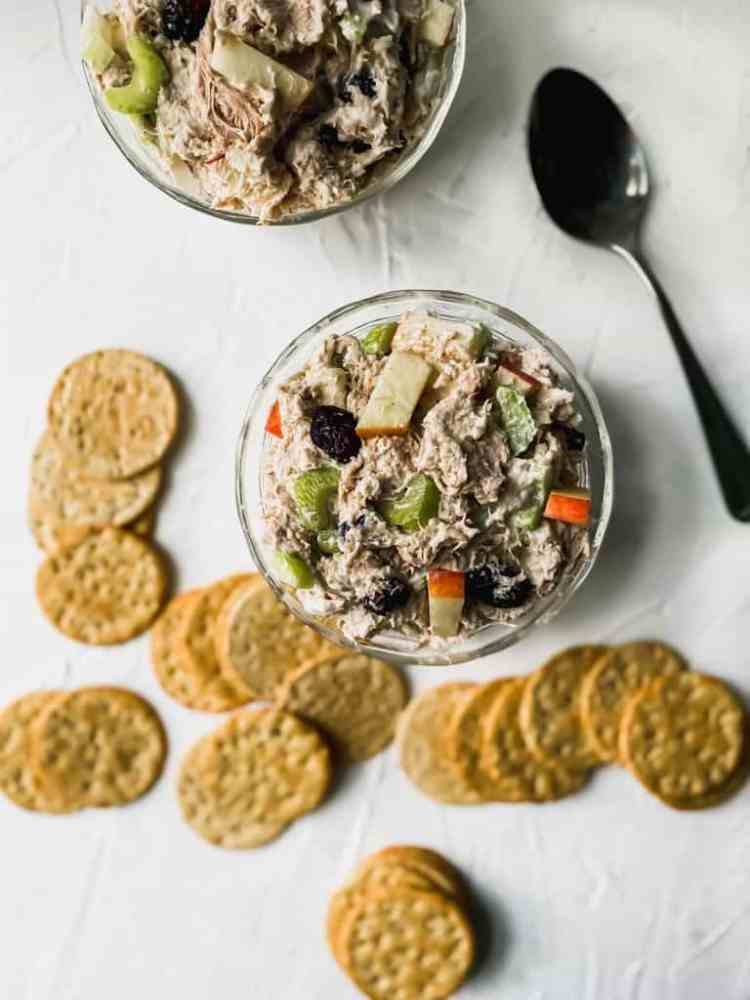 2 glass bowls of chicken salad with a spoon and crackers around them