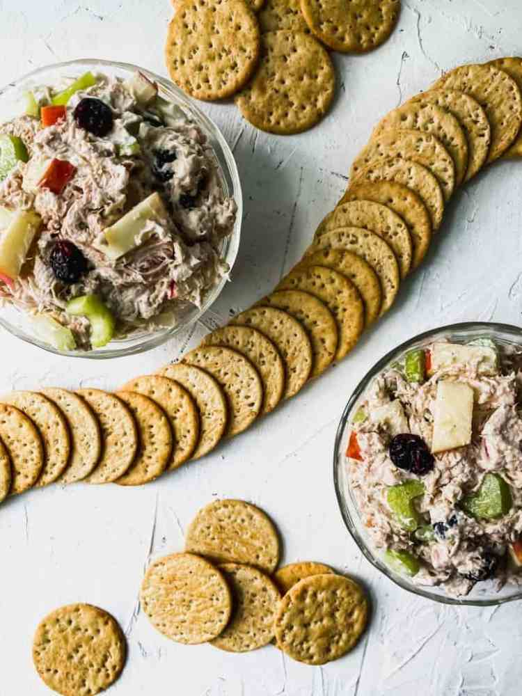 2 glass bowls of shredded chicken salad with cranberries and apples with crackers around them