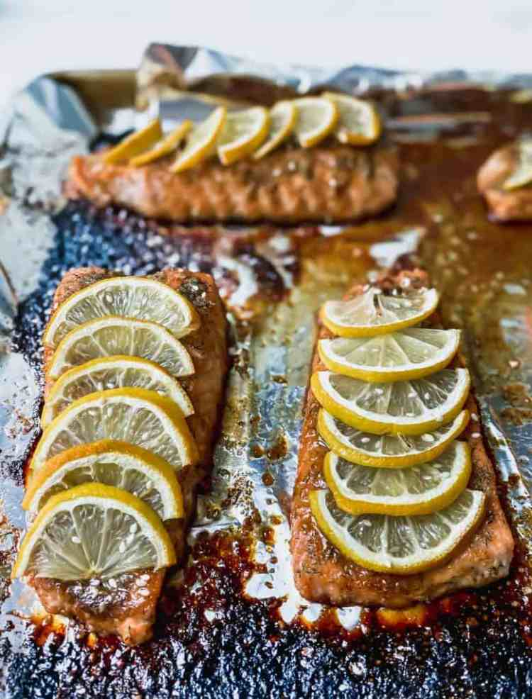 baked teriyaki salmon with lemon slices and some caramelized sauce on a foil lined sheet pan.