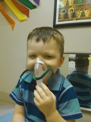 Grinning from behind the mask during his first ever breathing treatment, three years ago.