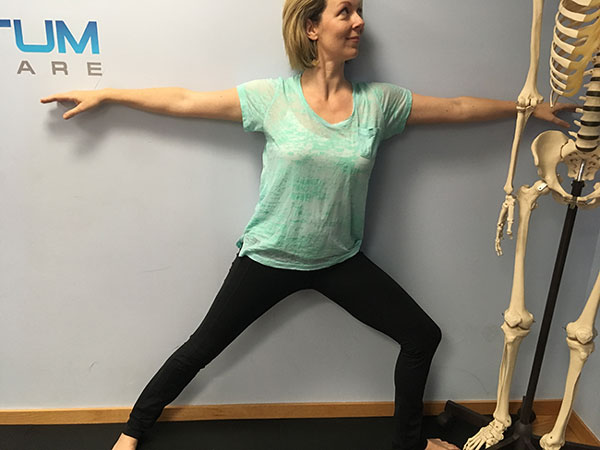 Lean against the wall for support while doing Warrior 2 pose during prenatal yoga
