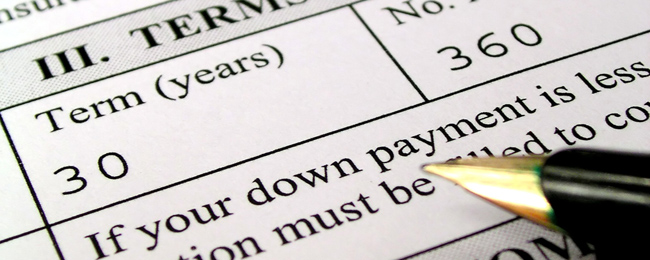 Hand with pen writing on a mortgage application - Video: Reverse Mortgages