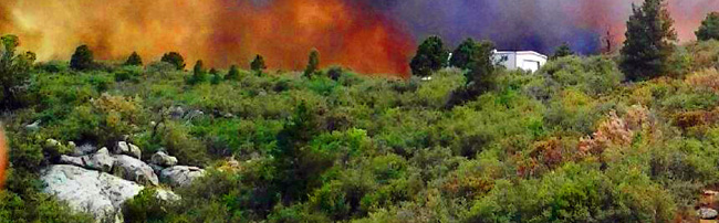 Wildfire approaching a home - HOA Wildfire Mitigation Policy