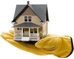 Yellow-gloved hand holding a little house - fixer upper, home improvement, buying a home as is - Bill salvatore, Arizona Elite Properties 602-999-0952 - Arizona Real Estate