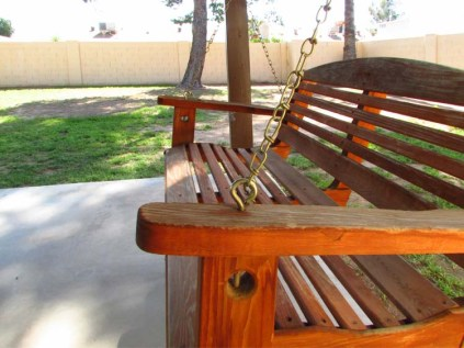 Close up of wooden chair-swing on concrete patio with gassy yard beyond - 783 W Park Ave, Chandler Arizona - Wood chair-swing on covered patio - Bill Salvatore, Arizona Elite Properties 602-999-0952 - Arizona Real Estate