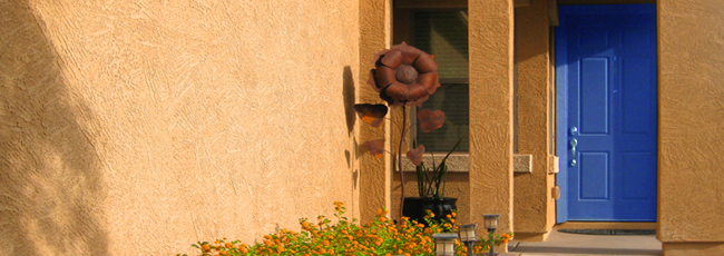 Sun shining on stucco home with bright blue door, walkway lined with yellow flowers and 6-foot metal sunflower sculpture - Welcoming front entrance - Bill Salvatore, Arizona Elite Properties 602-999-0952 - Arizona Real Estate