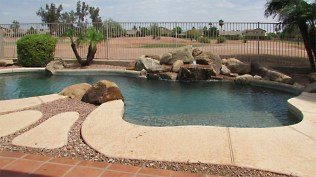 view across cool decking and pool toward water feature to fence and golf course - Pebble Tec Pool and Golf Course Lot - 1205 S Sandstone Street, Gilbert AZ 85396 - Western Skies Golf Community - Bill Salvatore, Arizona Elite Properties 602-999-0952 - Arizona Real Estate