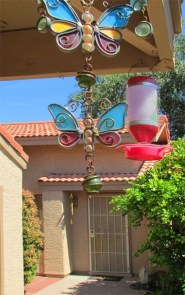 Bird feeders and wind chimes hanging in front courtyard with home entrance in the background - 945 N Pasadena, Mesa AZ - Park Centre Patio Homes - Bill Salvatore, Arizona Elite Properties 602-999-0952 - Arizona Real Estate