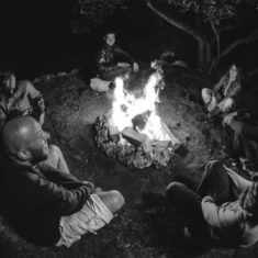 Image of people sharing stories and communicating to build consensus facilitated by a campfire