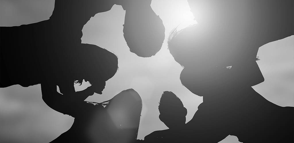 Silhouette of people embracing showing collaboration and leadership
