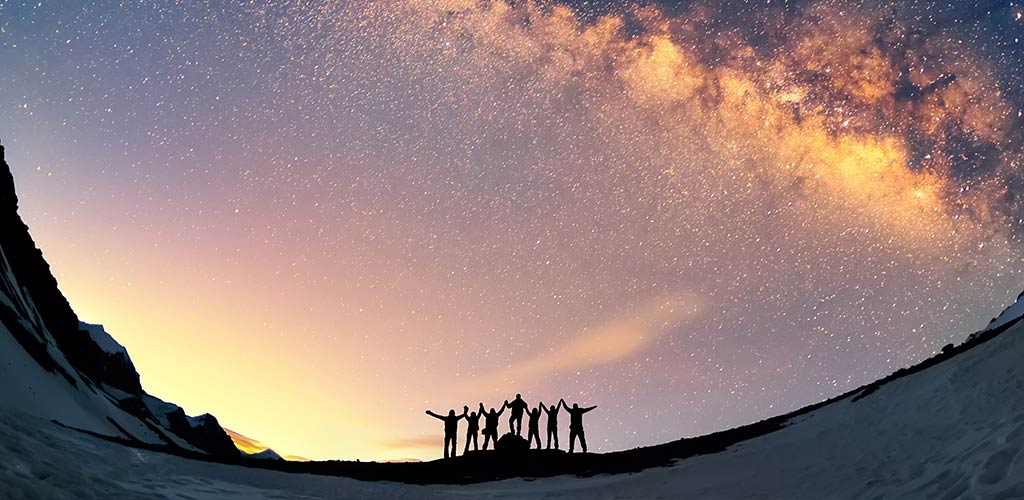 Amazement at the vision created through training. A group of people are standing together holding hands against the Milky Way in the mountains.