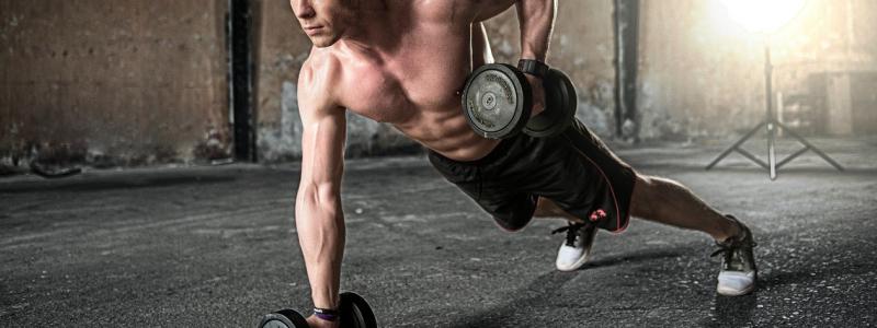 man exercising dumbbells gym