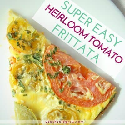 Slice of frittata with tomatoes and basil on a white plate with text overlay: super easy heirloom tomato frittata