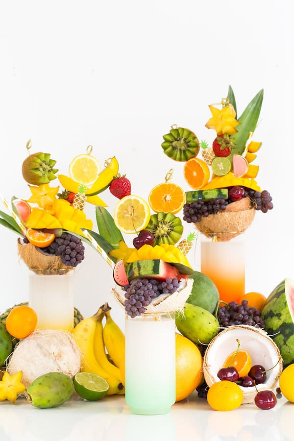 Skewers of tropical fruit on top of milkshake glasses