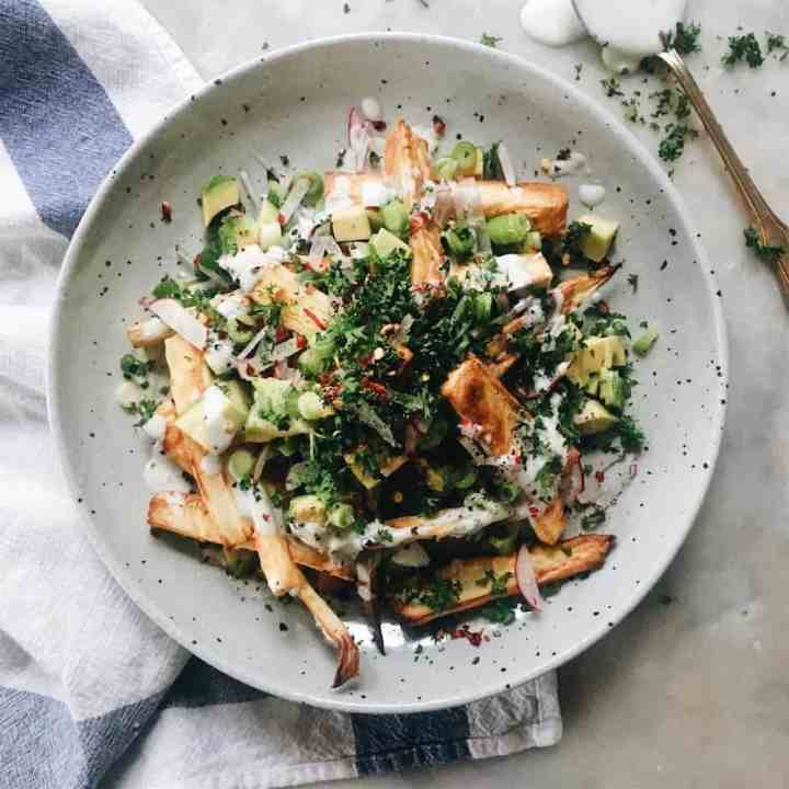 Parsnip fries with toppings on a white plate.