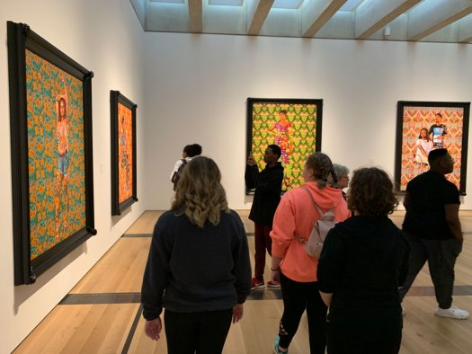 Six Youth Art Team artists viewing large Kehinde Wiley portraits in a gallery.