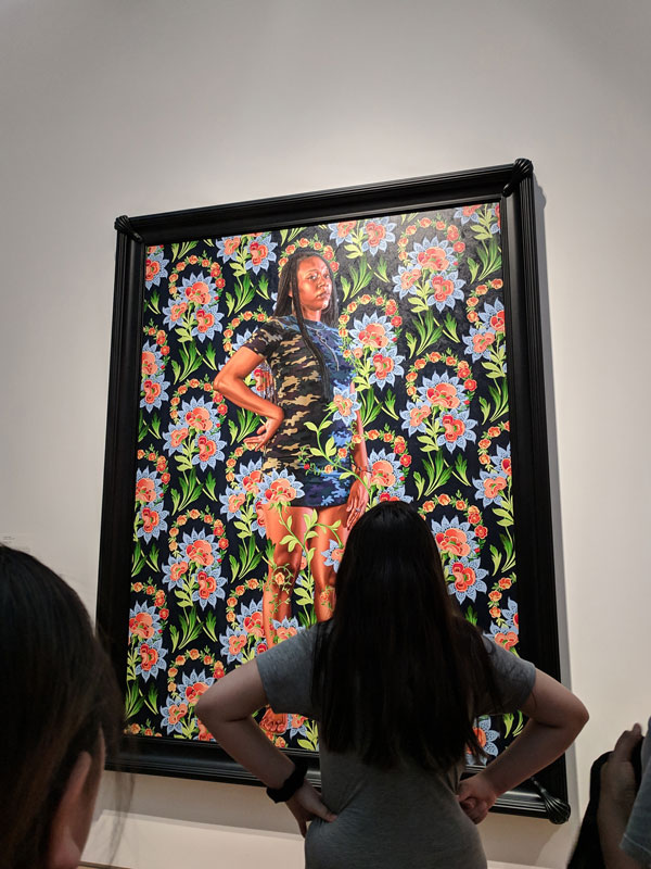 One Youth Art Team artist standing with her hands on her hips while viewing a large Kehinde Wiley portrait of woman standing with her hand on her hip.