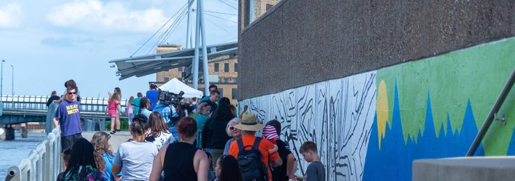 """People gathering at the """"Our Freedom Story"""" mural near the RiverLoop Amphitheatre at the Waterloo Center for the Arts"""