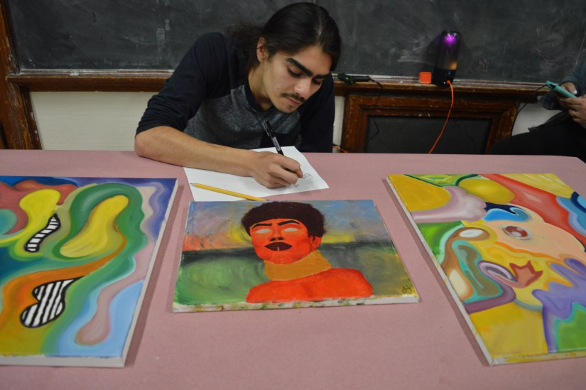 Youth at table showcasing his art