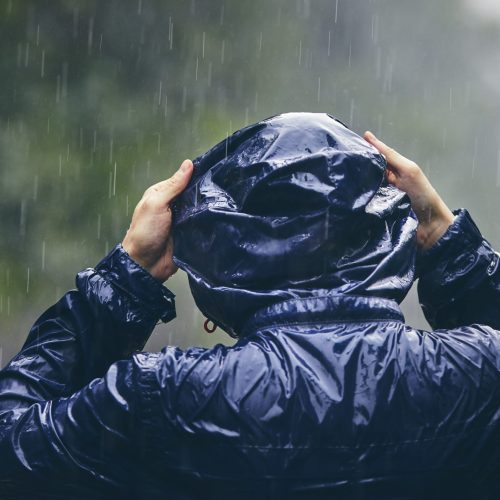Young person in heavy rain