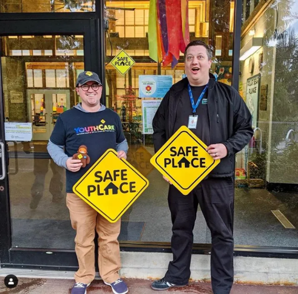 A Safe Place Response team hold up Safe Place signs