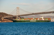 A colorful cargo ship on the move under the Bay Bridge...