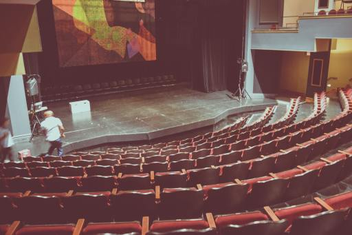 An empty theatre with a projection of different colours above the main stage.
