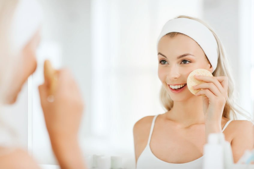 A woman with a headband on washing her face for great skin for fall