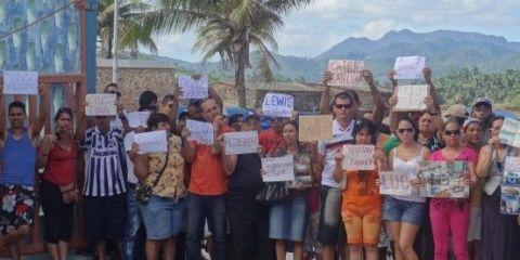 Cuba- Baracoa des personnes attendent avec panneaux pour les Casa Particular