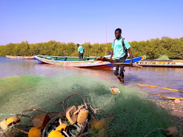 Un filet de pêche et un jeune local sur l'ile de Wandié dans l'Ile de Mar Lodj photo blog voyage tour du monde https://yoytourdumonde.fr