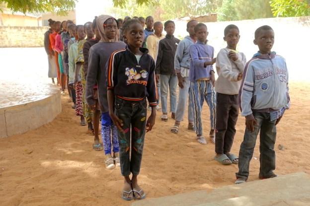 Les élèves de CM2 entrent dans une classe dans la localité de Mar Lodj dans le Sine Saloum. Photo blog voyage tour du monde https://yoytourdumonde.fr