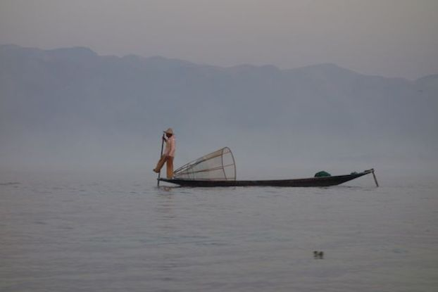 Certains pecheurs attendent les touristes sur le lac inle pour gagner un peu d'argent ici nous voyons un vrai pecheur qui attend le poisson photo blog voyage tour du monde https://yoytourdumonde.fr