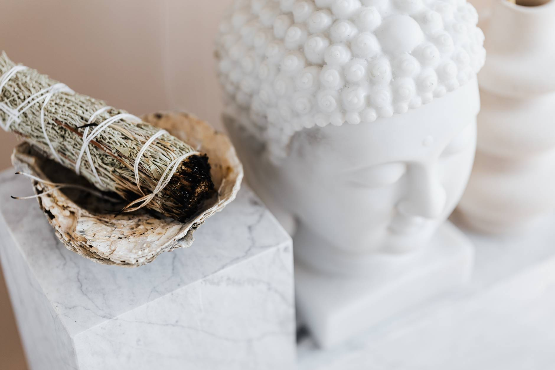 sage smudge stick in bowl on marble shelf near buddha head