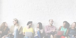 Image of a group people sitting and talking against a brick wall