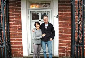 Antioch College's new president, Tom Manley, started at the college on March 1, replacing Mark Roosevelt, who left at the end of 2015. Manley is pictured here with his wife, Susanne Hashim, in the doorway of their home, the Folkmanis House on President Street. The couple moved to Yellow Springs with their young daughter, Chedin.  (Photo by Audrey Hackett)