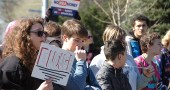 Local students gathered downtown for a rally last Friday, April 20, to commemorate the 19th anniversary of a school shooting at Columbine High School. Pictured are, from left, Mason Lindsey, JJ Bledsoe, Ellery Bledsoe and Mark Bricker (at rear). Students walked out of Yellow Springs High School/McKinney Middle School and marched downtown to express their support for stricter gun control measures and to urge the government to do more to improve school safety. (Photo by Megan Bachman)