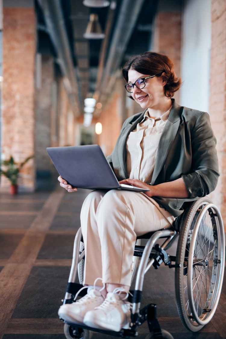 photo of woman sitting on wheelchair while using laptop