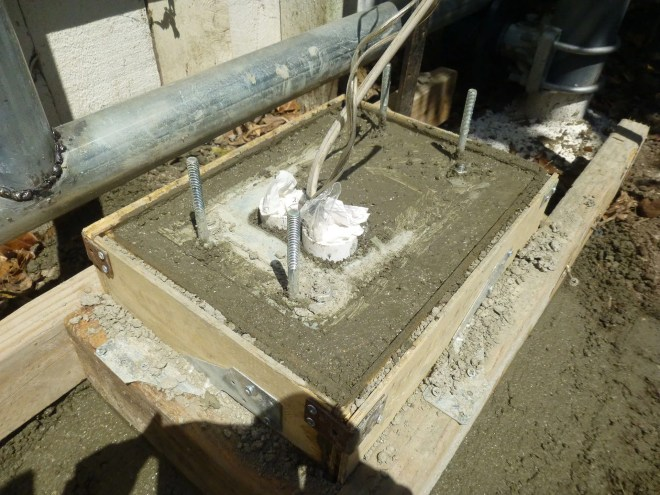 Concrete mix is still wet. Note the mounting bracket is placed on top of the mix with the four anchor bolts buried inside.