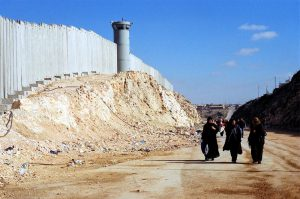 Palestinian women walk near Israel's barrier near Ramallah in the West Bank. Photo: IRIN/Shabtai Gold