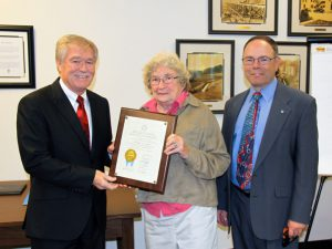 Tim Crough, left, accepts a retirement plaque from NID Board President Nancy Weber and General Manager Rem Scherzinger