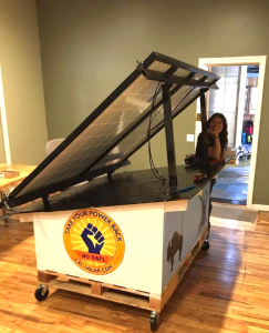 Laura Parkes of California Solar Electric Co. presents a mobile solar system to Community Organizer, Chris Jones. The mobile solar system will be taken to Standing Rock to provide power for journalists.