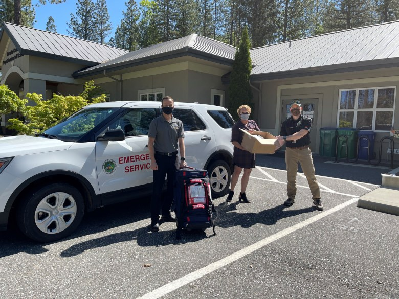 Nevada County Schools Superintendent Scott Lay and Director of School Safety Chris Espedal receive supplies from Nevada County Office of Emergency Services Program Manager Paul Cummings.