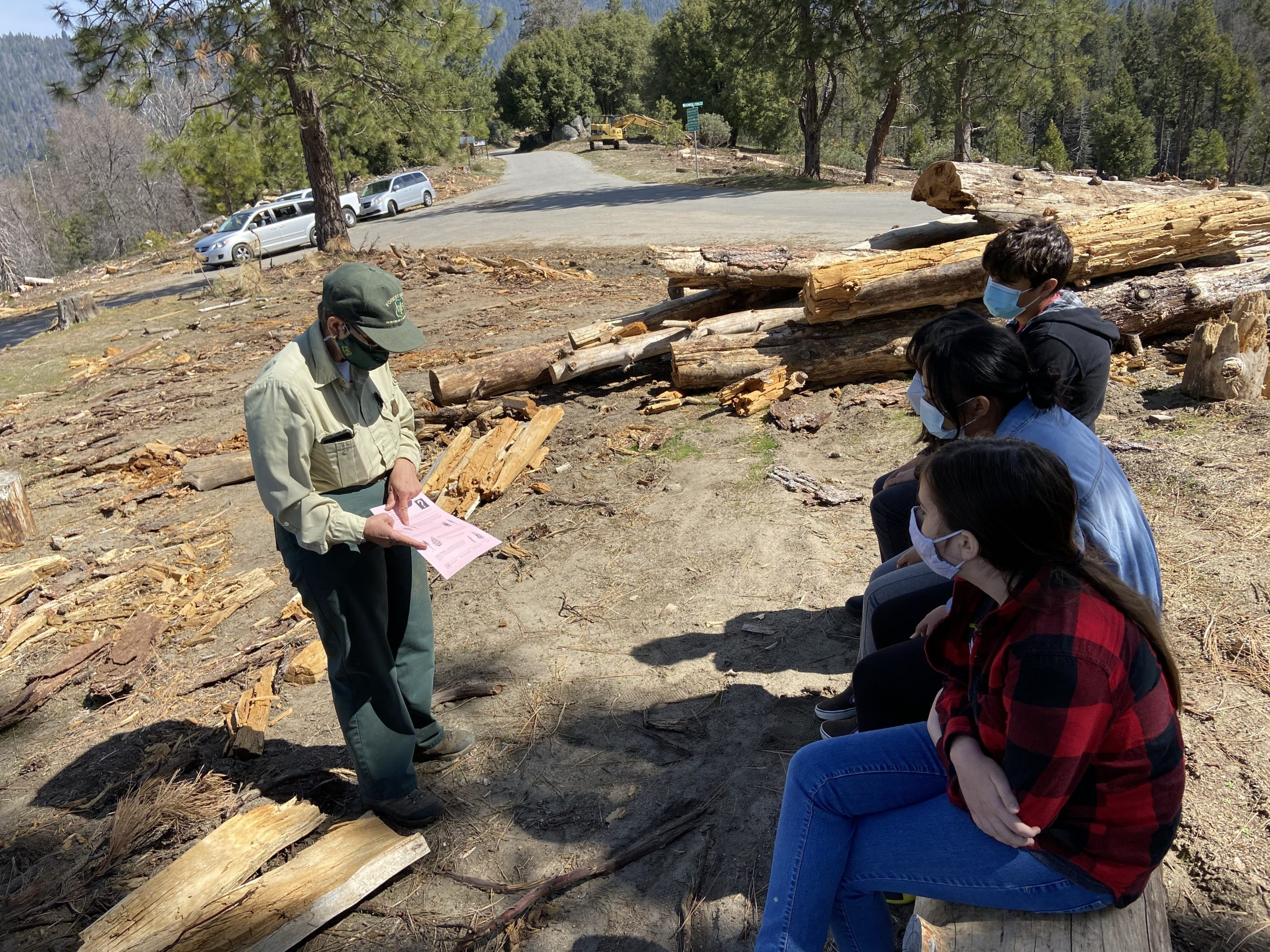 Marianne Emmendorfer, a Silviculturist with the Sequoia National Forest's Hume Lake Ranger District, describes the Eshom Ecological Restoration project to the team of four eighth-grade students before planting seedlings.