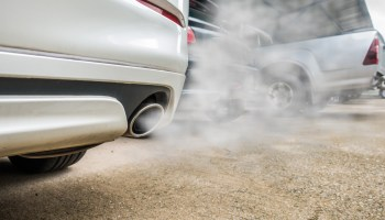 Combustion fumes coming out of white car exhaust pipe, air pollution concept.