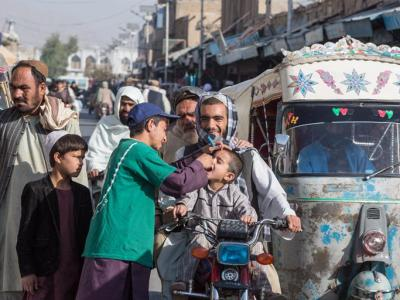 Abdhul Rahman, polio vaccination volunteer, gives oral polio vaccine to an Afghan boy on a busy street. 2019 file photo by WHO/G. Elham