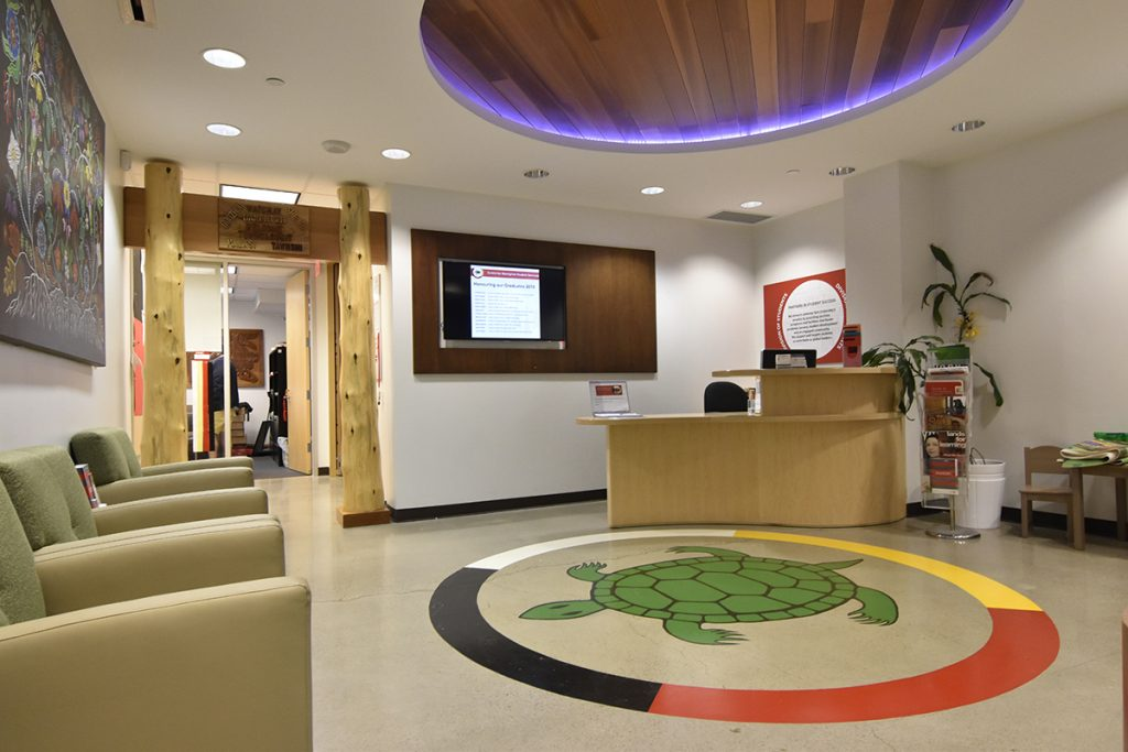 Front office of CASS. Reception area with painting of turtle on the floor and an illuminated roof.