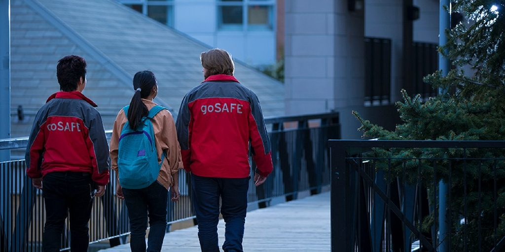 A young woman being accompanied by two people in goSafe jackets.