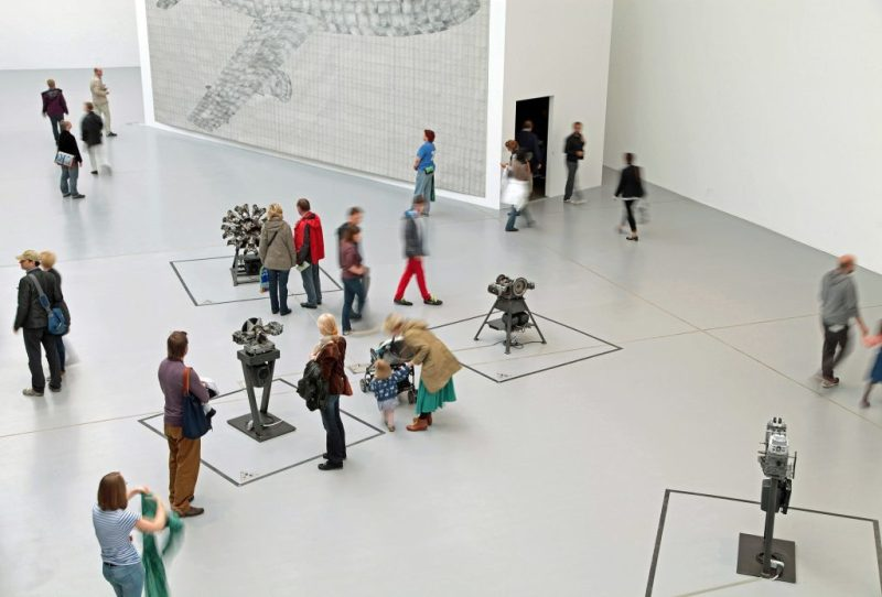 Image of people walking in modern art exhibit in white room from a bird's eye view perspective by Pilot Brent from Pixabay