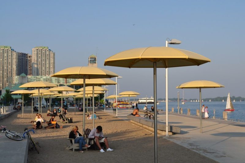 Image of a beach and people sitting under beach umbrellas at Queens Quay by Skeeze from Pixabay